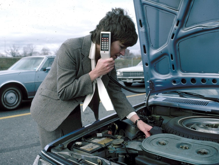 Image: A stranded motorist calls a service station from an in-car cellular phone, 1983, in a staged photo from General Electric.
