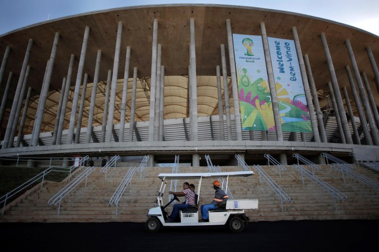 Image: Workers drive a cart in front of the National Stadium