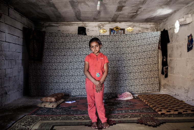 Image: Najua, 9, stands in the tiny shop front room where she lives with her mother Meyada and two brothers in Reyhanli, Turkey.