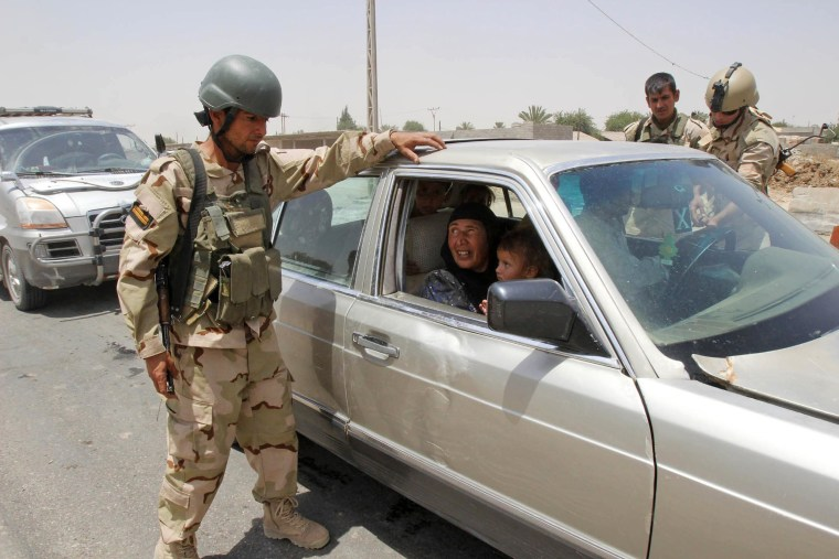 Image: Members of the Kurdish security forces check identification papers at a checkpoint during an intensive security deployment on the outskirts of Kirkuk