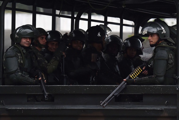 Image: Members of the Brazilian army are seen as they leave after escorting the England football team to their hotel in Rio de Janeiro