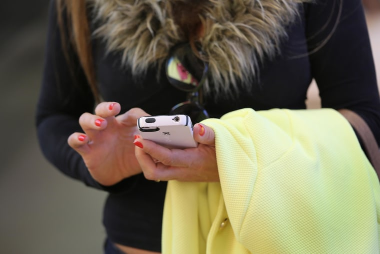 Image: A woman uses an Iphone at Apple's Fifth Avenue store on Earth Day in Midtown Manhattan on April 22 in New York City.