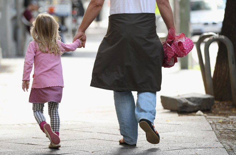 Image: A father and daughter walk in a city center