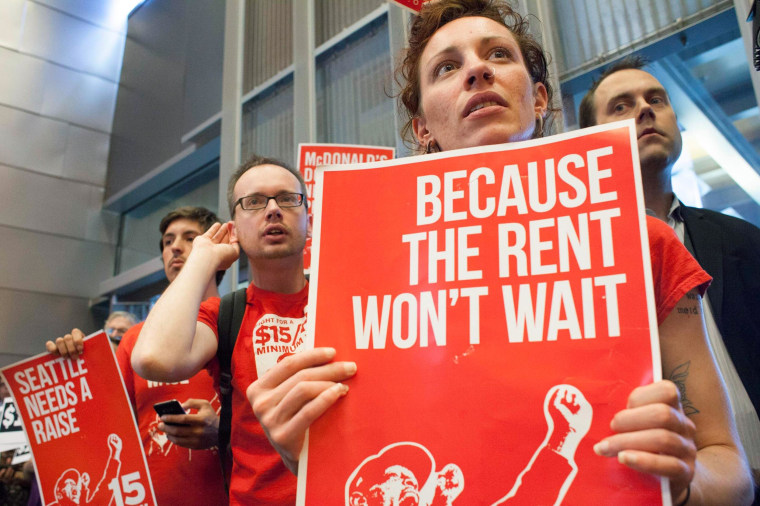 Image: Labor activists Ginger Jentzen and Jeremy Thornes listen during a Seattle City Council meeting in which the council voted on raising the minimum wage to $15 per hour in Seattle, Washington