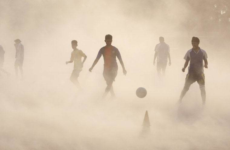 Aspiring young Indian soccer players continue with their practice during a dust storm in Jammu, India, Wednesday, June 11, 2014. Soccer fans around the world are gearing up to watch the Soccer World Cup that begins in Brazil Thursday.