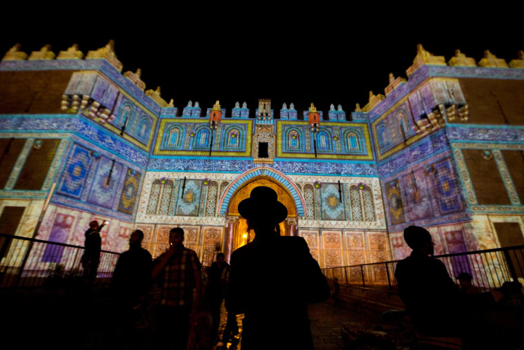 An Ultra Orthodox Jewish man watches a light projection show at the Damascus Gate during the Jerusalem Lights Festival, in the Old City of Jerusalem, Israel, early June 12, 2014.