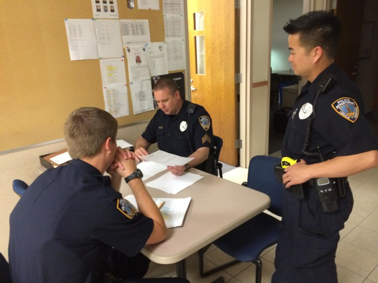 Lincoln Police Officer Tu Tran meets with other officers before heading out on patrol.