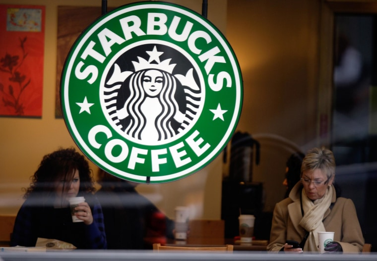 Image: Customers drink coffee and check messages inside a Starbucks Coffee store