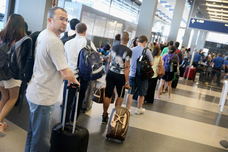 Image: Passengers wait in line to check in for flights at O'Hare International Airport on May 23, 2014, in Chicago.
