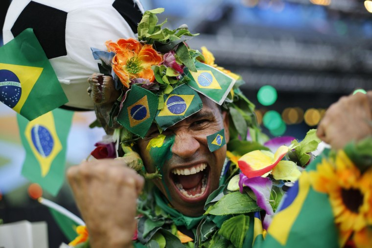 Image: A Brazil soccer fan covered in flowers and his nation's flag cheers inside the FIFA Fan fest area before the start of the World Cup soccer game between Brazil and Croatia