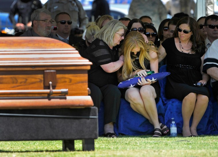 Image: Andrea Soldo, center, is consoled by family members after receiving a flag during the funeral services for her husband, Las Vegas police officer Igor Soldo
