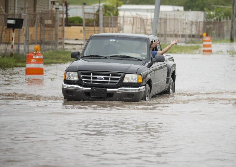 A man inside a truck gestures about the flood water depth in Medley, Florida, after severe weather hit the region in May.