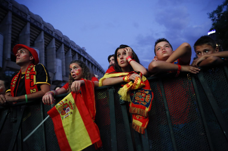 Spain supporters react as they watch the team's 2014 World Cup Group B  soccer match against Netherlands on a giant screen at a fan park in Madrid on June 13.