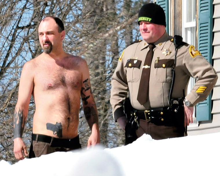 Image: Michael Smith, left, bearing a realistic-looking tattoo of a handgun on his stomach