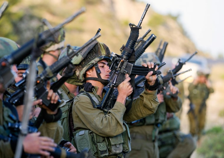 Image: Israeli soldiers load their weapons near Hebron