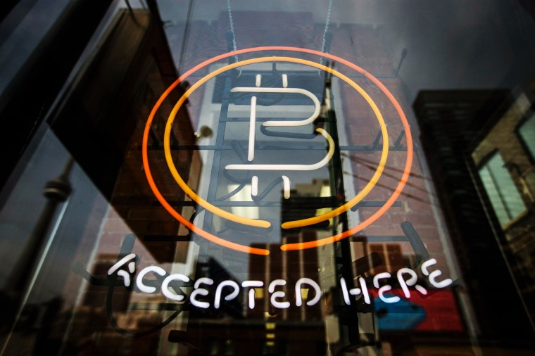 Image: A Bitcoin sign is seen in a window in Toronto