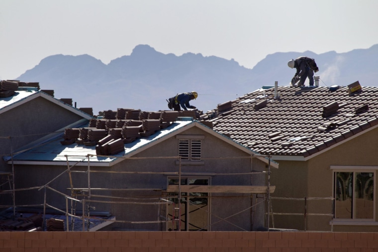 Roofers work on new homes at a residential construction site in the west side of the Las Vegas Valley.