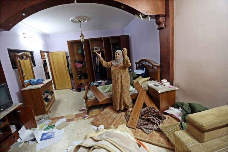 Image: Eyad Terawe checks the damage to her family home after Israeli troops arrest her son