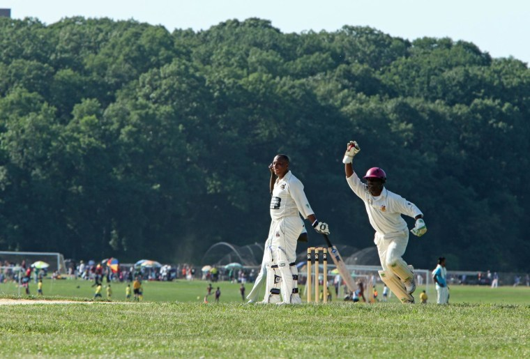 A player holds up the ball after catching it during a cricket match in Van Cortlandt Park in Bronx, N.Y.