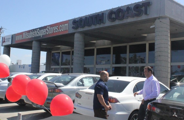 Abbas Ahmadi, right, talks with an employee at his South Coast Mitsubishi dealership in Costa Mesa, Calif.