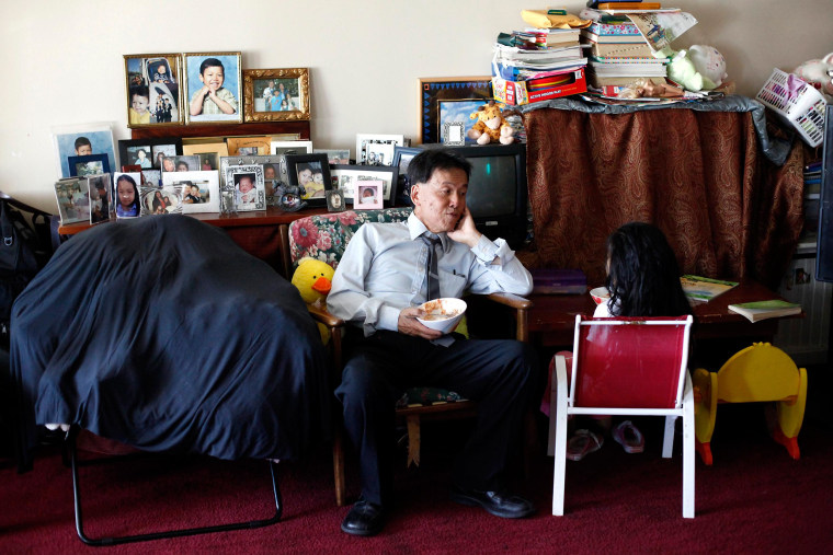 Alan Choy chats with his daughter Yvania, 8, about her day at their home in San Francisco, on June 17, 2014. The Choys, who receive Social Security Disability Insurance, are struggling financially.