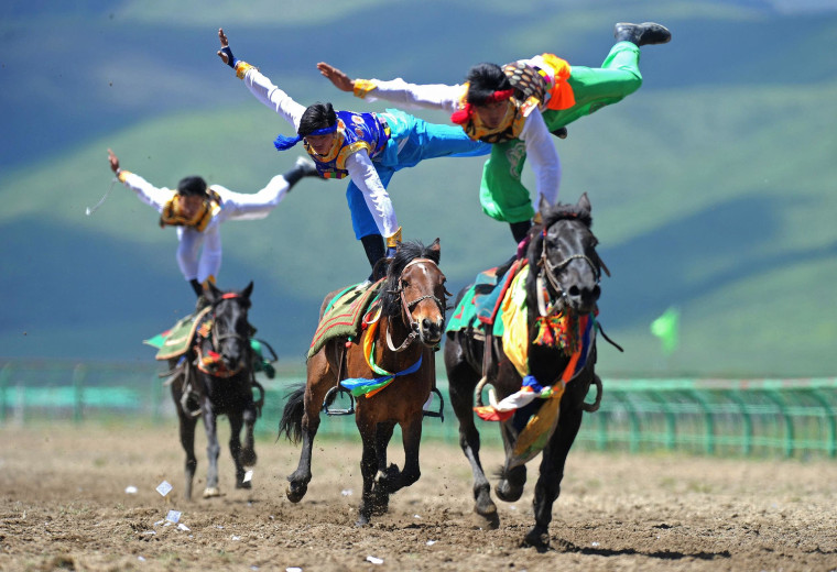 Image: Riders wearing ethnic group costume competing in a traditional horseback riding event