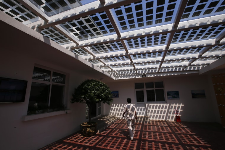Image: A man walks inside an office building of Yingli Solar in Baoding
