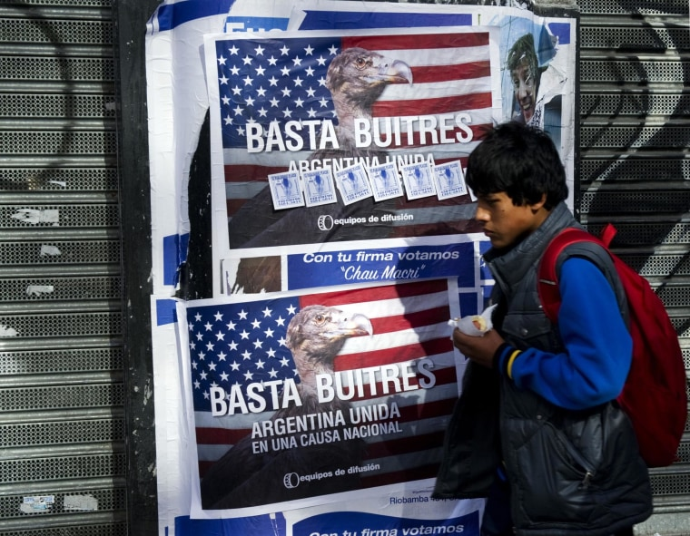 """Image: A young man passes by posters on a wall against """"vulture funds"""" in Buenos Aires"""