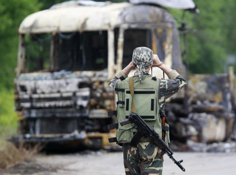 Image: A pro-Russian separatist stands guard at a checkpoint near a burnt truck outside Luhansk