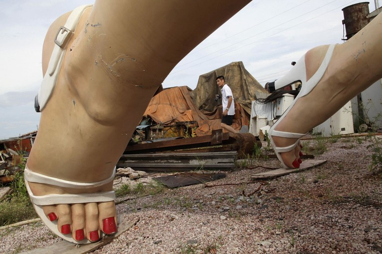 Image: Man walks past the feet of a giant statue of U.S. actress Marilyn Monroe at the dump site of a garbage collecting company in Guigang