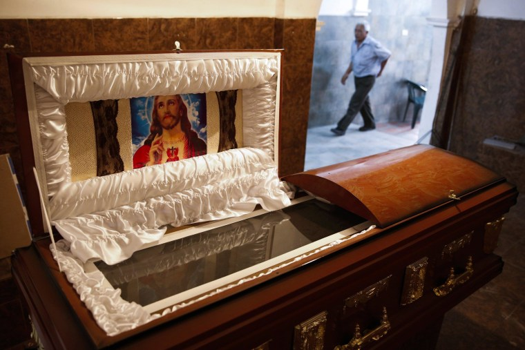 Image: A man walks behind an empty coffin at an undertaker's showroom in Caracas
