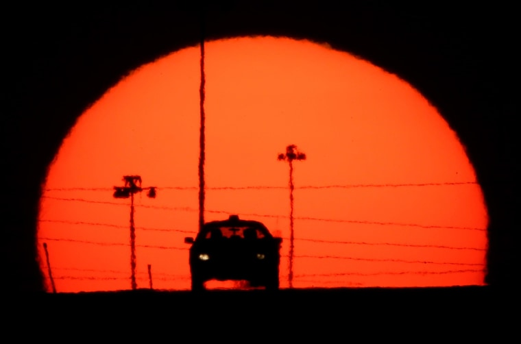 Image: A car is silhouetted against the setting sun