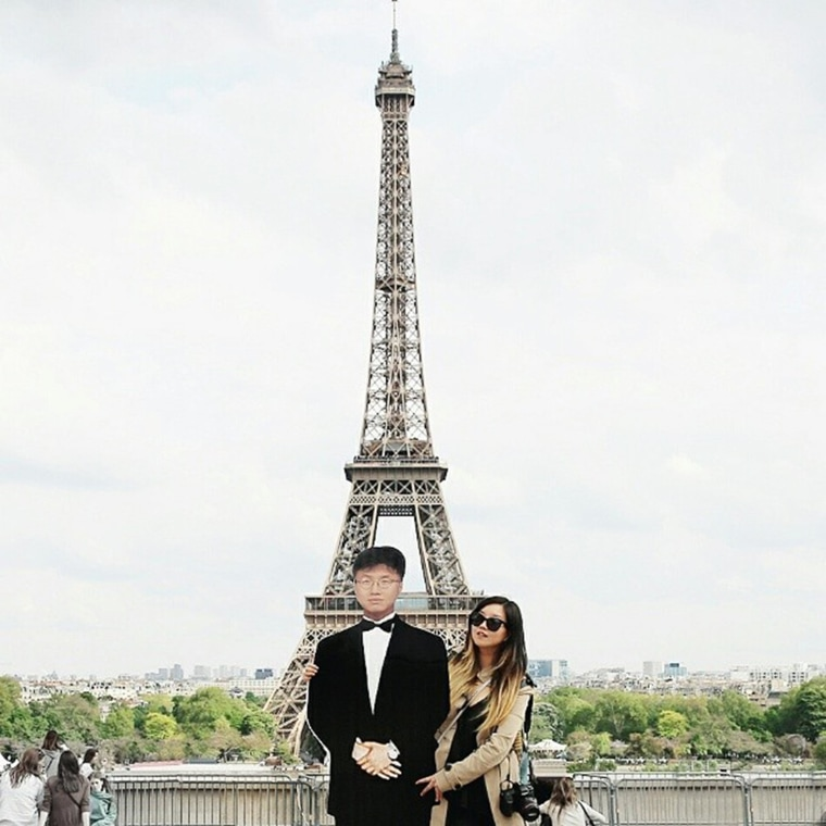 Image: Jinna stands with a cardboard cutout of her father in front of the Eiffel Tower