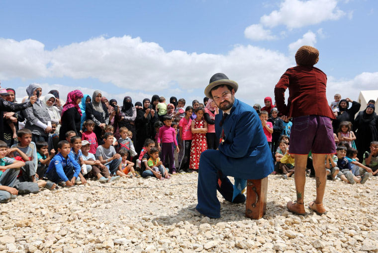"""Chilean clown Claudio, right, and American clown David Clay, left, members of """"Clowns Without Borders,"""" perform for children at a Syrian refugee camp in the eastern town of Chtoura, in Bekaa valley, Lebanon on  June 6, 2014."""