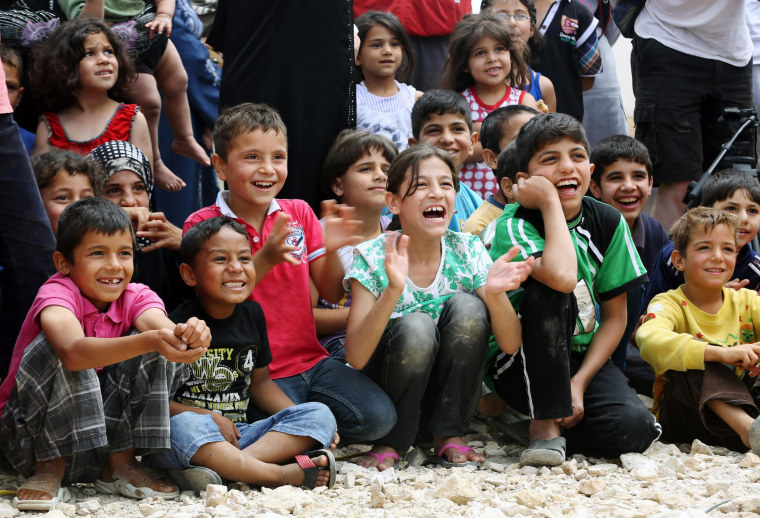 """Image: Syrian refugee children smile while watching members of """"Clowns Without Borders"""""""