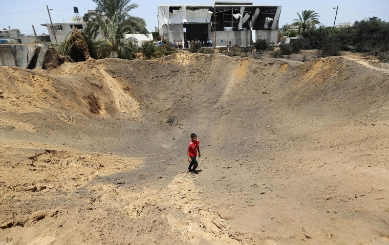 Image: A Palestinian man walks inside a crater made by an Israeli airstrike