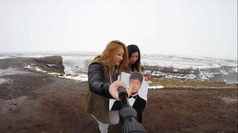 Jinna Yang and a friend prepare to take a photo with a cardboard cutout of Yang's late father.