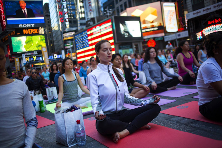 Image: People practice yoga in Times Square as part of a Summer Solstice celebration in New York