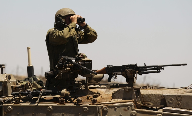 Image: An Israeli soldier uses binoculars on the Israeli-Syrian border in the Golan Heights
