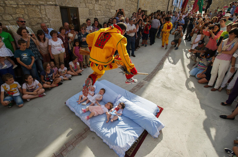 A man representing the devil leaps over babies during the festival of El Salto del Colacho (the devil's jump) on June 22, 2014 in Castrillo de Murcia, Spain. The festival, held on the first Sunday after Corpus Christi, is a catholic rite of the devil cleansing babies of original sin.