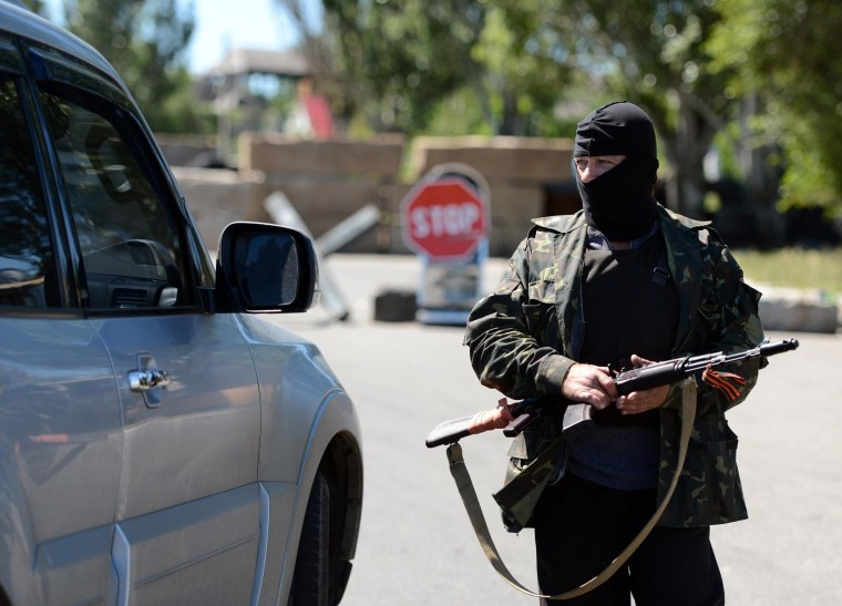 Image: A Russian separatist controls a car on the checkpoint in Sloviansk, Ukraine