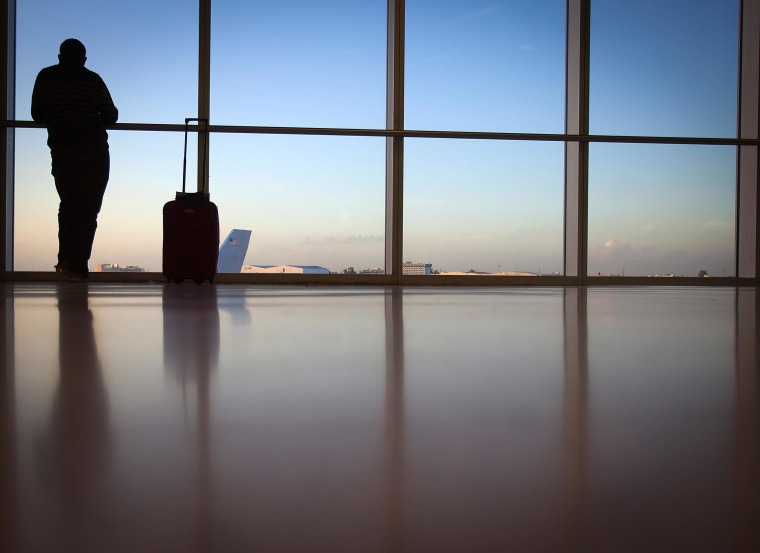 Image: A passenger looks out the window at Miami International Airport in Miami
