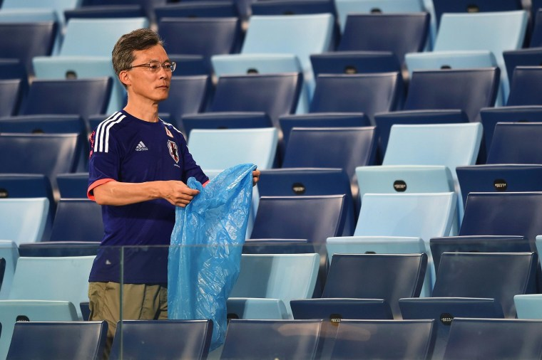 Image: A Japan fan helps collect litter from the stadium