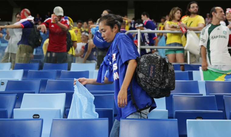 Image: A Japan fan helps collect litter from the stadium after the Japan and Colombia match on Tuesday.