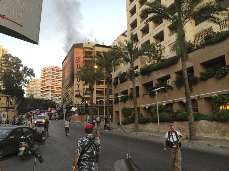 Image: Policemen and security officials secure the area as smoke rises from Duroy hotel in Raouche