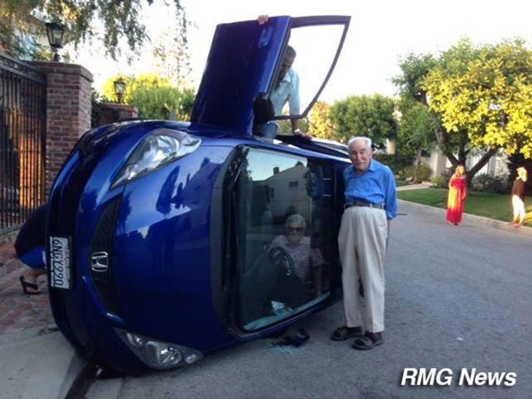 Image: An elderly couple poses with their flipped car
