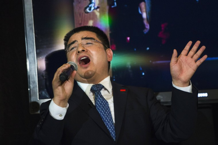 """Image: Chinese millionaire Chen Guangbiao sings """"We Are the World"""" during a lunch he sponsored for hundreds of needy New Yorkers at Loeb Boathouse in New York's Central Park"""