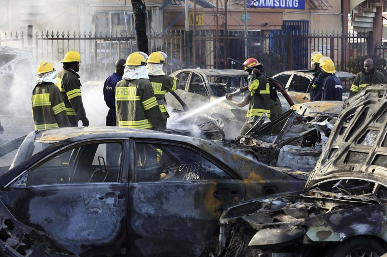 Image: Firefighters douse cars after a bomb blast at a crowded shopping district in Abuja