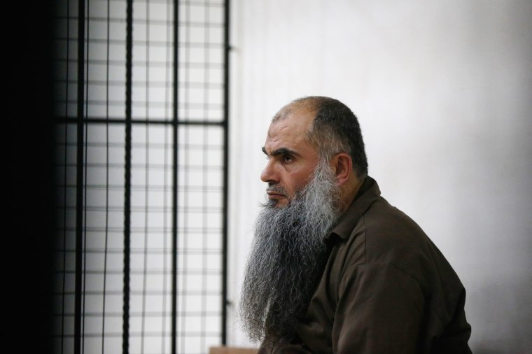 Image: Radical Muslim cleric Abu Qatada looks on from behind bars at the State Security Court in Amman