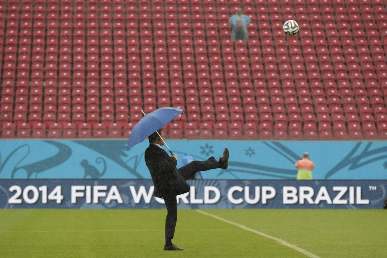 A FIFA official tests the pitch as rain pours down prior to the group G World Cup soccer match between the USA and Germany at the Arena Pernambuco in Recife, Brazil, on June 26.